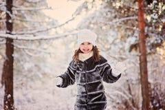 Winterporträt des netten lächelnden Kindermädchens auf dem Weg im sonnigen schneebedeckten Wald Lizenzfreies Stockbild