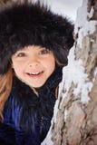 Winterporträt des netten lächelnden Kindermädchens auf dem Weg im sonnigen schneebedeckten Wald Stockfotografie