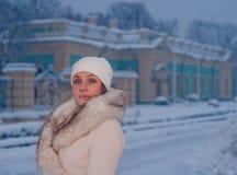 Winterporträt einer Frau im weißen Mantel und im Hut während der Schneefälle in einem Park Stockfotografie