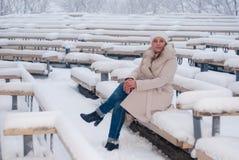 Winterporträt einer Frau im weißen Mantel während der Schneefälle in einem Park Stockbild