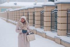 Winterporträt einer Frau im weißen Mantel während der Schneefälle in einem Park Stockbilder