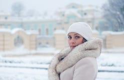 Winterporträt einer Frau im weißen Mantel während der Schneefälle in einem Park Lizenzfreie Stockfotografie