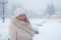 Winterporträt einer Frau im weißen Mantel während der Schneefälle in einem Park Lizenzfreie Stockbilder