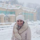 Winterporträt einer Frau im weißen Mantel während der Schneefälle in einem Park Stockfotos
