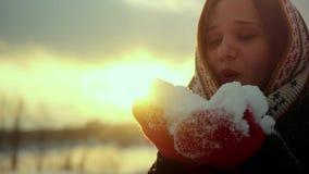 Winterporträt einer schönen jungen Frau brennt Schneeflocken und das Lächeln in der Zeitlupe während der Sonnenuntergangzeit mit  stock video