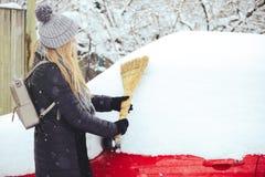 Winterporträt eines Reinigungsschnees der jungen Frau von einem Auto Schönheit blondes vorbildliches Girl lacht und säubert nett  Lizenzfreies Stockfoto