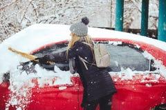 Winterporträt eines Reinigungsschnees der jungen Frau von einem Auto Schönheit blondes vorbildliches Girl lacht und säubert nett  Stockbilder