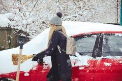 Winterporträt eines Reinigungsschnees der jungen Frau von einem Auto Schönheit blondes vorbildliches Girl lacht und säubert nett  Lizenzfreies Stockbild