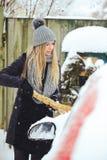 Winterporträt eines Reinigungsschnees der jungen Frau von einem Auto Schönheit blondes vorbildliches Girl lacht und säubert nett  Stockbild