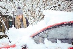 Winterporträt eines Reinigungsschnees der jungen Frau von einem Auto Schönheit blondes vorbildliches Girl lacht und säubert nett  Lizenzfreie Stockbilder