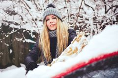 Winterporträt eines Reinigungsschnees der jungen Frau von einem Auto Schönheit blondes vorbildliches Girl lacht und säubert nett  Lizenzfreie Stockfotografie