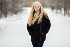 Winterporträt: junge Blondine kleideten in einer warmen woolen Jacke an, die draußen in einem schneebedeckten Park aufwirft Stockfotografie