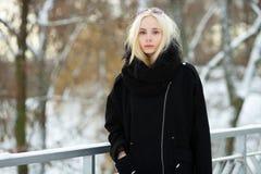 Winterporträt: junge Blondine kleideten in einer warmen woolen Jacke an, die draußen in einem schneebedeckten Stadtpark aufwirft Stockbild