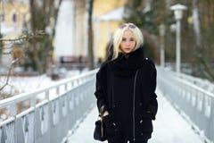 Winterporträt: junge Blondine kleideten in einer warmen woolen Jacke an, die draußen in einem schneebedeckten Stadtpark aufwirft Lizenzfreies Stockfoto