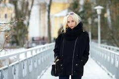 Winterporträt: junge Blondine kleideten in einer warmen woolen Jacke an, die draußen in einem schneebedeckten Stadtpark aufwirft Lizenzfreie Stockfotos