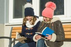 Winterporträt von netten jungen Freundstudenten auf einer Bank mit Büchern, positiven Leuten und Freundschaftskonzept lizenzfreie stockbilder