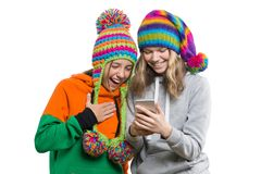 Winterporträt von zwei glücklichen schönen Jugendfreundinnen in den Strickmützen, die Spaß mit Handy, lokalisiert auf Weiß haben lizenzfreie stockfotos