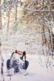 Winterporträt des netten glücklichen Kindermädchens im grauen Pelzmantel spielt mit Schnee im Wald Lizenzfreie Stockfotos