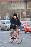 Winters dressed woman on a bike, Beijing, China Royalty Free Stock Photo