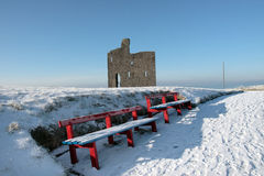 Winters path to ballybunion castle and red benches. A seasonal snow covered view of atlantic ocean and ballybunion castle with red benches on a frosty snow Royalty Free Stock Photos