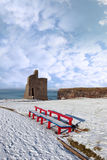 Winters view of ballybunion castle and red benches. A seasonal snow covered view of atlantic ocean and ballybunion castle with red benches on a frosty snow Royalty Free Stock Photo