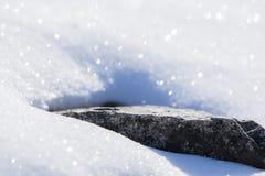Wintersaisonschneebedeckte Grundbeschaffenheit, die im Sonnenlicht mit dem lokalisierten Felsen heraus die Hauptrolle spielt funk Stockfotos