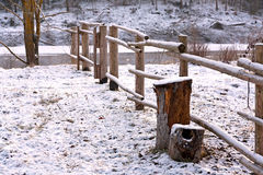 Winterscene - wooden fence. Rural nature seasonal scene: wooden fence in winter forest near a river covered by snow Stock Images
