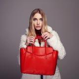 Winterschönheit im Pelz-Mantel Schönheits-Mode-Modell Girl stilvolles blondes Luxusmädchen mit roter Handtasche Stockfotografie