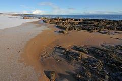 Winterschnee auf Dornoch-Strand Stockfoto