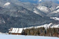 Winterschneebedeckte Karpatenberge und alte ruinierte hölzerne Halle, Großbritannien Lizenzfreie Stockfotos