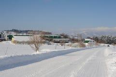 Winterschneelandschaft mit schneebedeckter Straße Stockfotos
