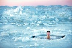 Winterschwimmen. Mann in einem Eisloch Stockbilder