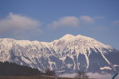 Wintersierra bedeckt im Schnee unter klarem Himmel und Wolken Stockfotografie