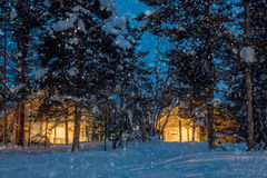 Wintersnowfallnacht, kleine blokhuizen met warm licht Royalty-vrije Stock Foto's