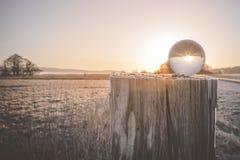 Wintersonnenaufgang mit Sonne in einer Glaskugel lizenzfreie stockbilder
