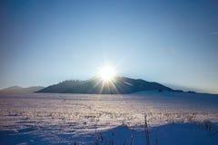 Wintersonnenstrahlen über schneebedeckter Wiese in Liptov Poludnica im Hintergrund lizenzfreie stockfotografie