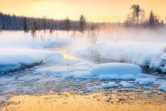 Wintersonnenuntergang im Wald und im Fluss mit schönem nebelhaftem Nebel Stockbild