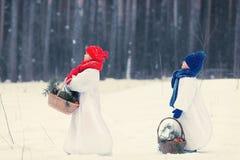 Winterspaß, glückliches Kind, das mit Schneemann spielt Lizenzfreie Stockfotos