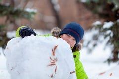 Winterspaß, glückliches Kind, das mit Schneemann spielt Stockfotografie