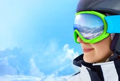 WinterSport, Snowboarding - portrait of young snowboarder girl at the ski resort. A Mountain Range Reflected in the Ski Mask Royalty Free Stock Image