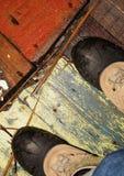 Winterstiefel auf einem nassen Bretterboden Lizenzfreie Stockbilder