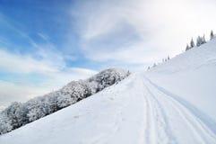 Winterstraße, die auf Hügeloberseite läuft Lizenzfreie Stockfotos