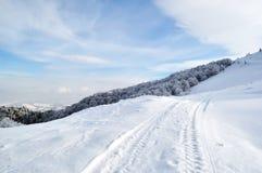 Winterstraße, die auf Hügeloberseite läuft Stockfotos