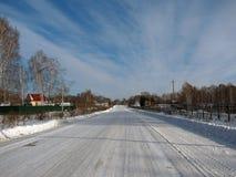 Winterstraße durch den Wald Lizenzfreies Stockfoto