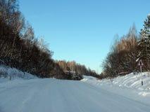 Winterstraße durch den Wald Stockfotos