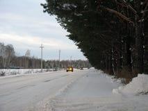 Winterstraße durch den Wald zum Dorf Lizenzfreie Stockfotografie