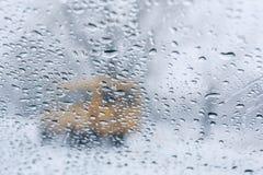 Winterstraße durch nasse Windschutzscheibe Lizenzfreies Stockbild