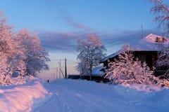 Winterstraße nahe bei einem Holzhaus Stockbild