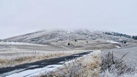 Winterstraße in Rolling Hills durch die Ackerlande bedeckt mit Nebel und Schnee Lizenzfreie Stockfotografie