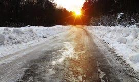 Winterstraße und -wald bei Sonnenuntergang Stockbild